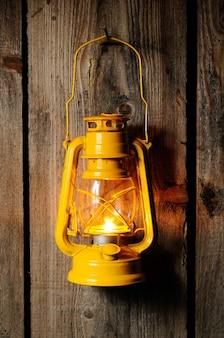 A velha lanterna de querosene pendurada na parede de madeira