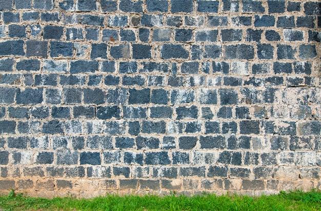 A velha parede de tijolos e grama verde