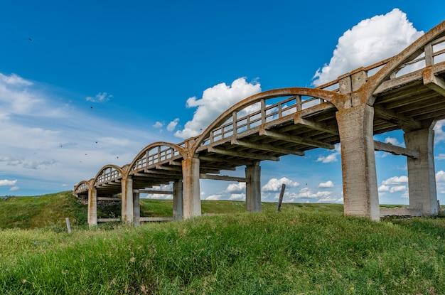 A velha ponte de concreto coberta de líquen em scotsguard, sk com grama verde em primeiro plano