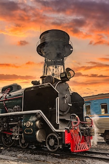 A velha velha locomotiva a vapor no fundo do sol.
