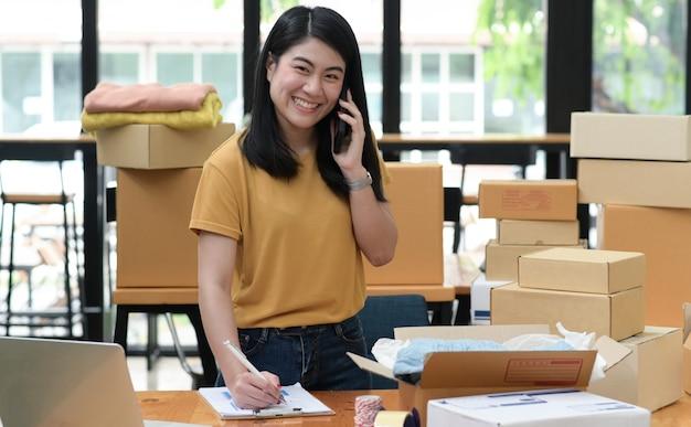 A venda online feminina liga para o telefone e faz anotações e recebe pedidos com um sorriso. a caixa do pacote é colocada na mesa, ela olha para a câmera e sorri.