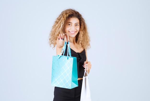 A vendedora arrumou as sacolas coloridas e deu para o cliente.