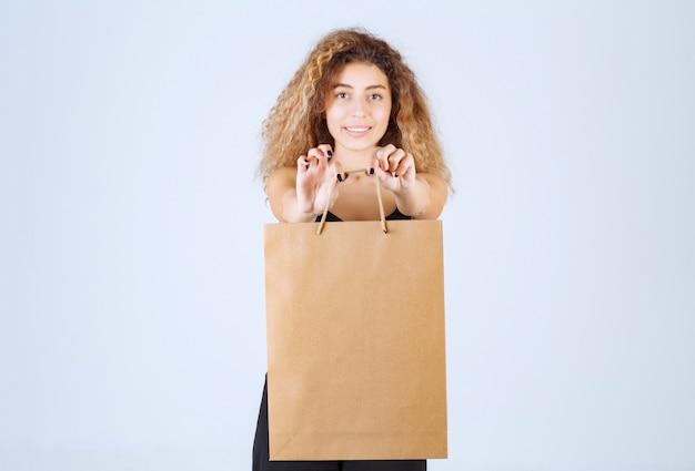 A vendedora embalou as coisas em uma sacola de papelão e as ofereceu ao cliente.