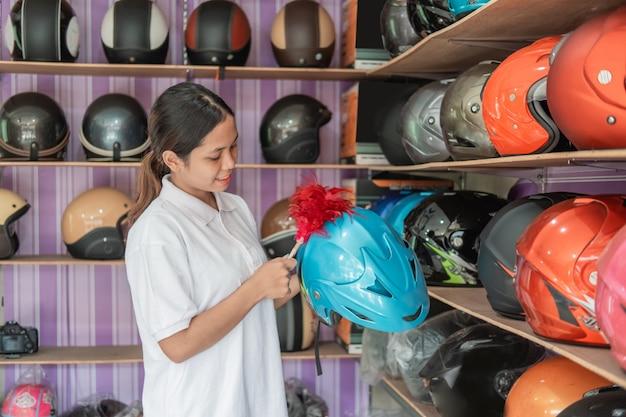 A vendedora feminina fica limpando um capacete com um espanador na loja de capacetes