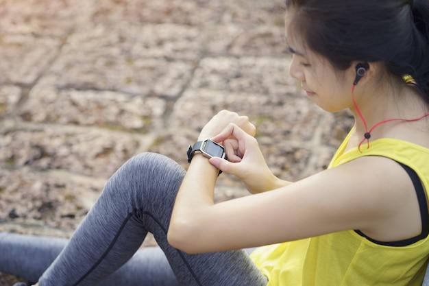 A verificação do progresso da mulher no relógio esperto conecta escuta a música ao fone de ouvido, dispositivo de aptidão wearable.