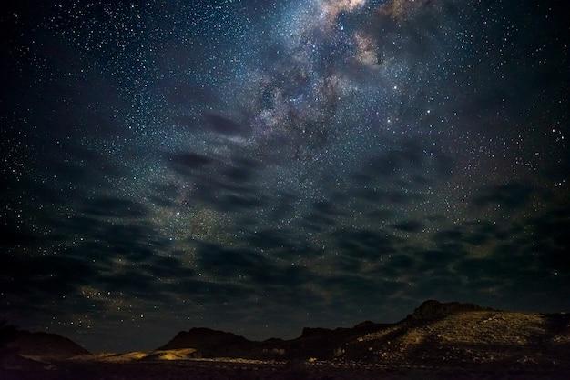 A via látea protagoniza no céu, o deserto de namib em namíbia, áfrica. algumas nuvens cênicas.
