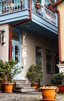A vida nas ruas estreitas de old tbilisi, com estradas de pedra, casas de tijolos vermelhos e varandas e janelas entalhadas