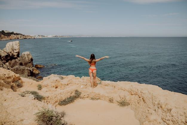 A viewgirl de costas em maiô vermelho, com os braços erguidos e posando na praia