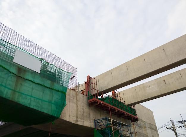 A viga de concreto do monotrilho da grande estação está em construção próximo ao subúrbio da metrópole, vista frontal para o espaço da cópia.