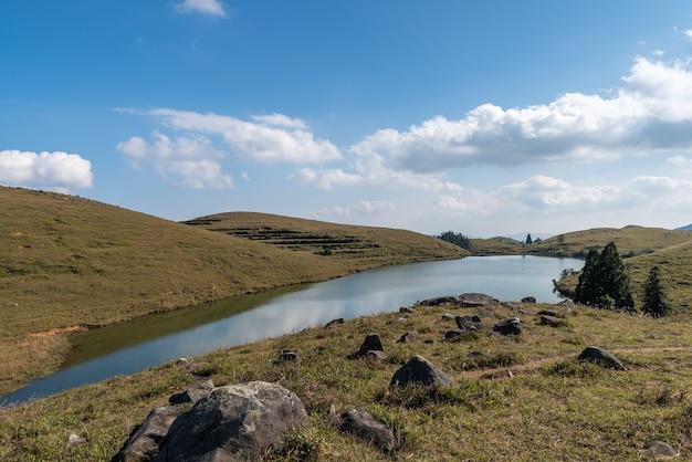 A visão completa do lago natural na pastagem, com céu azul, águas claras e grama amarela