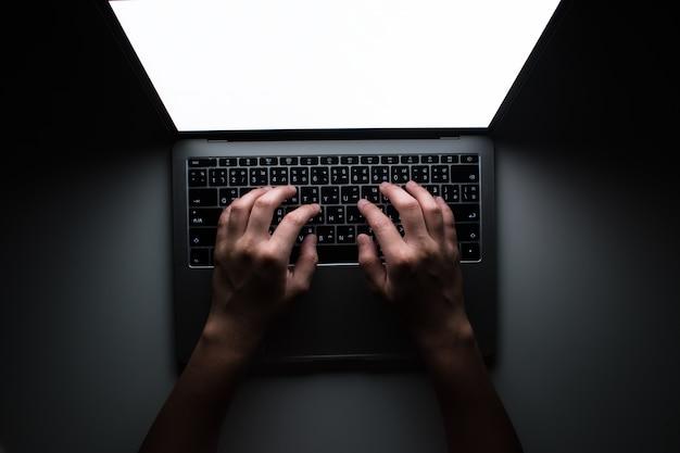 A visão de cima do programador está trabalhando em uma sala escura em uma mesa branca.