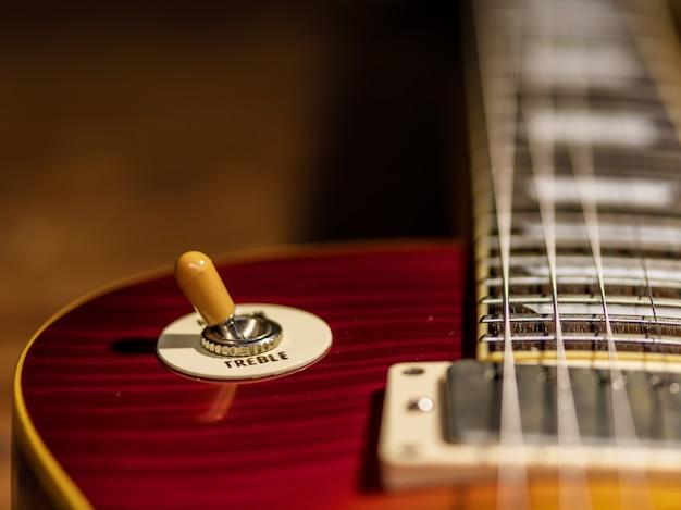 A visão em close do corpo da guitarra elétrica é no piso de madeira