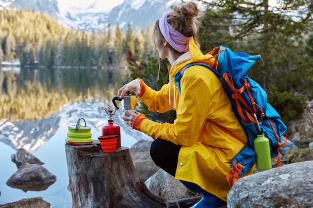 A visão externa de uma jovem usa equipamento turístico para fazer café e tem um fogão a gás portátil no toco
