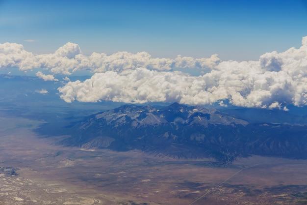 A visão geral do avião de nuvens fofas nas montanhas de um avião arizona eua