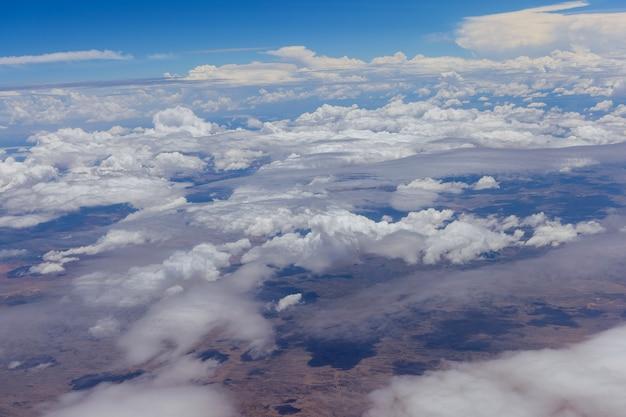 A visão geral do avião de nuvens fofas no deserto de montanhas de um avião novo méxico eua