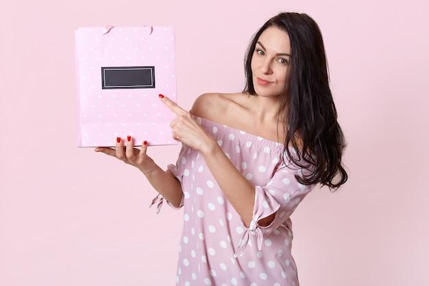 A visão horizontal da mulher europeia de aparência agradável aponta para a sacola de presente, mostra espaço livre para o seu conteúdo ou promoção de publicidade, vestido com um vestido de bolinhas, com manicure vermelho. tiro isolado