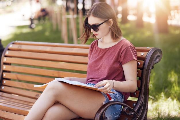 A visão horizontal de estudante sério usa óculos de sol da moda, camiseta casual e shorts jeans, concentrados no livro, senta-se no banco, posa no parque, ocupado com a aprendizagem e o estudo. conceito de educação