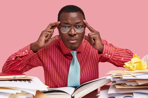 A visão horizontal de um adulto masculino negro estressante mantém as duas mãos nas têmporas, tem um olhar perplexo e usa óculos transparentes