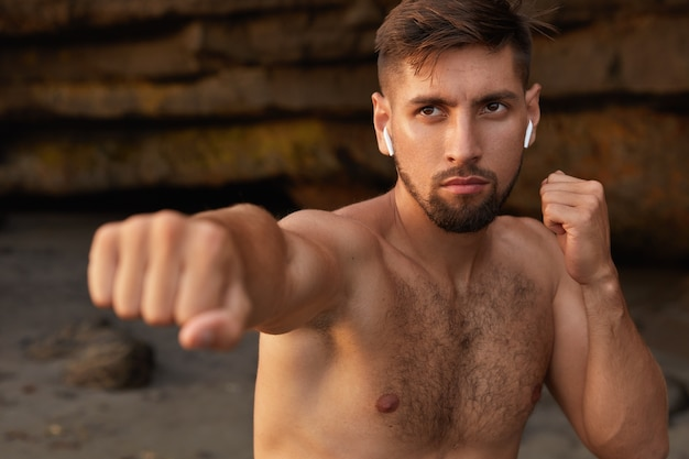 A visão horizontal de um boxeador masculino poderoso e concentrado pratica diferentes truques