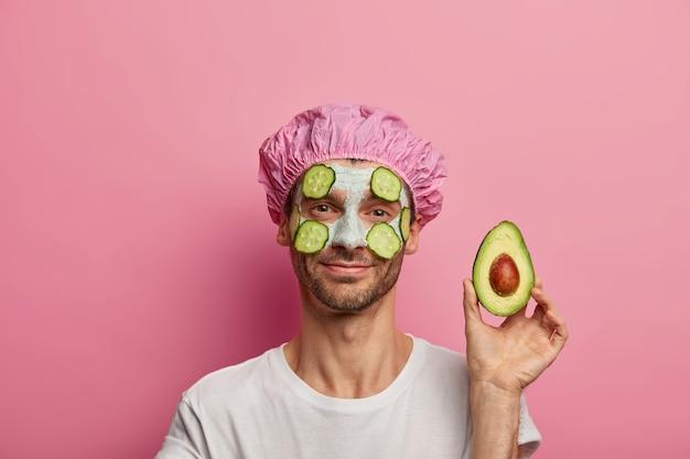 A visão horizontal de um jovem caucasiano satisfeito mostra metade do abacate, gosta de nutrir máscara de argila no rosto, tem barba por fazer, vestido com uma camiseta branca