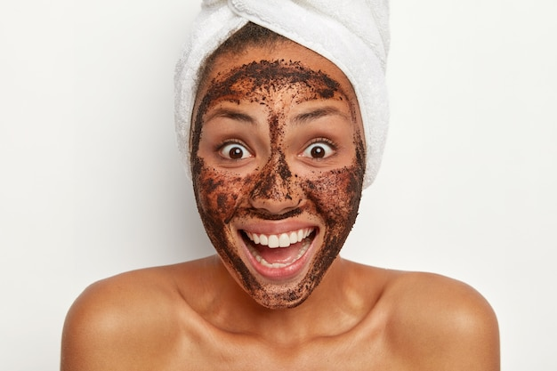 A visão horizontal de um modelo bonito de pele escura abre amplamente os olhos, sorri amplamente, gosta de tratamentos faciais em ambiente doméstico, usa uma toalha branca macia na cabeça, modelos contra a parede branca