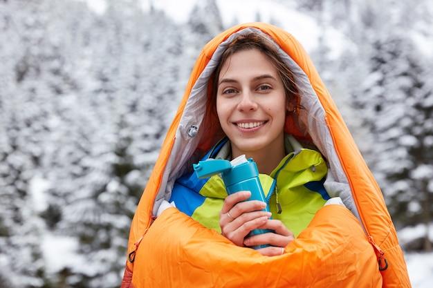 A visão horizontal de um turista atraente sorridente sente frio após uma expedição em montanhas nevadas