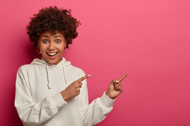A visão horizontal de uma jovem alegre com uma expressão alegre mostra a direção à parte, demonstra uma promoção incrível, mostra o caminho para um café, sugere a leitura da faixa, vestida com um capuz branco. propaganda