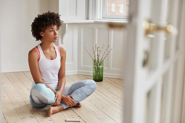 A visão horizontal de uma mulher contemplativa de pele escura faz as pernas dobradas, vestida com roupas casuais, tem descanso após o treino matinal