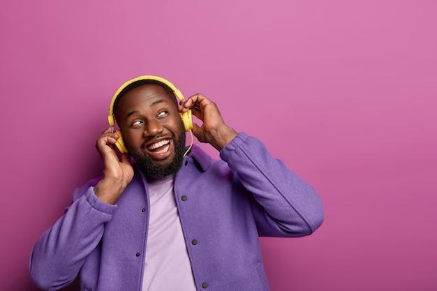 A visão horizontal do cara positivo usa fones de ouvido estéreo nas orelhas, gosta de música ao vivo, olha de lado, sendo melomano da música, vestido casualmente, tem um hobby