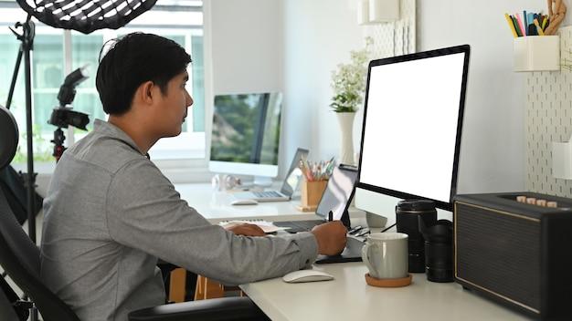 A visão lateral do designer gráfico ou fotógrafo está usando a mesa gráfica para retocar uma foto em seu espaço de trabalho.