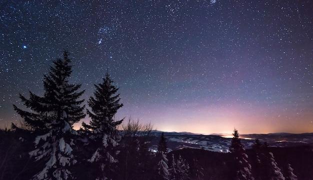 A visão mágica do céu estrelado claro se espalhou pela estação de esqui à noite em um clima frio e sem nuvens no inverno.