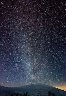 A visão mágica do céu estrelado e claro se espalha pela estação de esqui à noite em um clima frio e sem nuvens no inverno