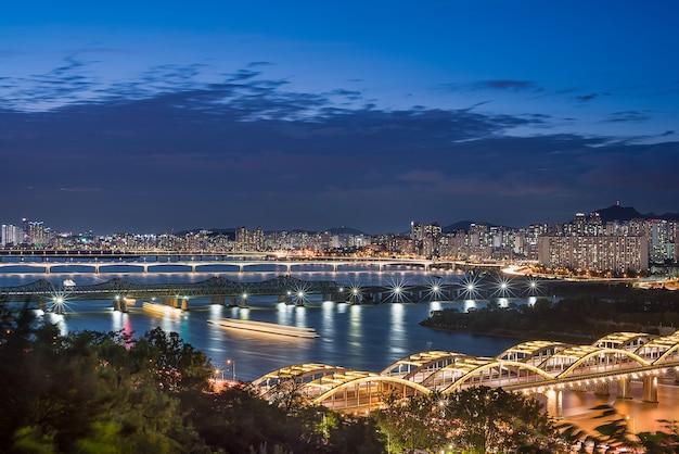 A visão noturna de seul com um barco de turismo