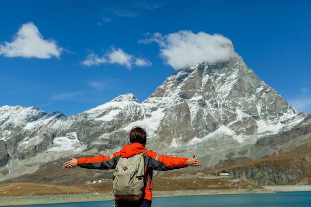 A visão traseira da mulher feliz e livre está em frente ao espaço matterhorn alpine copy