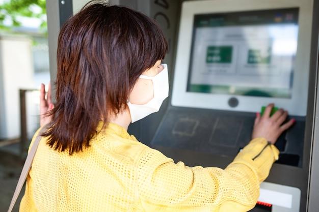 A visão traseira de uma mulher não identificada com uma máscara protetora aponta o dedo para um painel de informações embaçado com instruções para proteção contra coronovírus