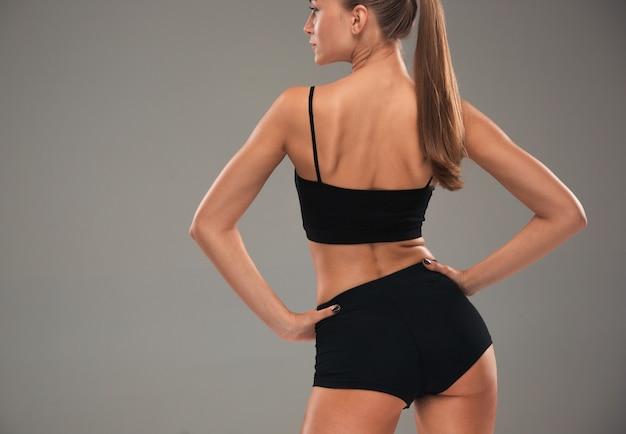 A visão traseira do atleta jovem musculoso posando no fundo cinza do estúdio