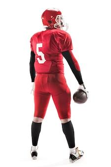 A visão traseira do homem caucasiano fitness como jogador de futebol americano segurando uma bola em branco