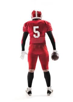 A visão traseira do homem caucasiano fitness como jogador de futebol americano segurando uma bola no fundo branco