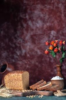 A visão vertical do pão preto dietético espiga os trigos na tábua de madeira e vasos de flores no fundo azul marrom com cores misturadas