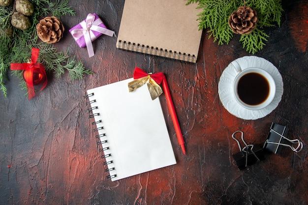A vista acima do abeto ramifica uma xícara de acessórios de decoração de chá preto e um presente ao lado do caderno com uma caneta em fundo escuro