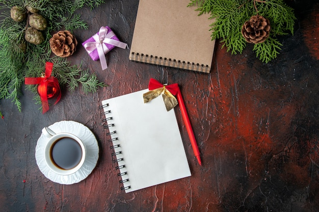A vista acima do abeto ramifica uma xícara de acessórios de decoração de chá preto e um presente ao lado do caderno com uma caneta na filmagem de fundo escuro