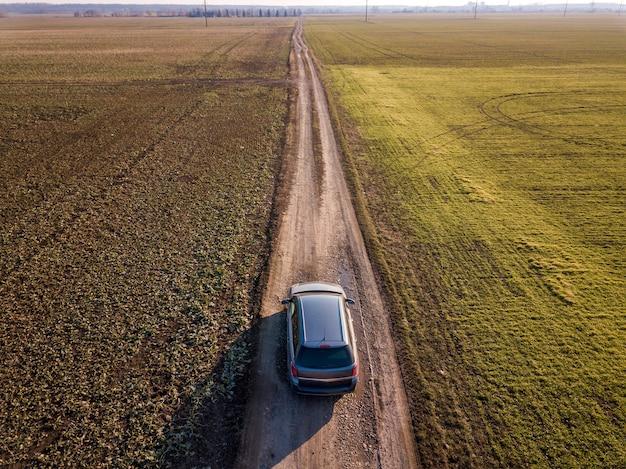 A vista aérea da condução de carro pela estrada à terra reta através dos campos verdes no céu azul ensolarado copia o fundo do espaço. fotografia de zangão.
