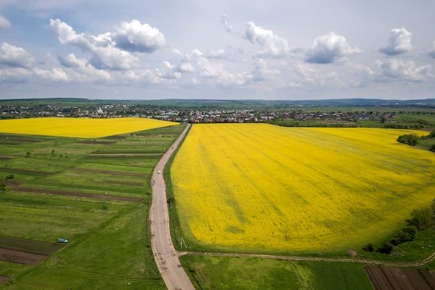 A vista aérea da estrada à terra com os carros em movimento em campos verdes com as plantas de colza de florescência, as casas do subúrbio no horizonte e o céu azul copiam o fundo do espaço. fotografia de zangão.