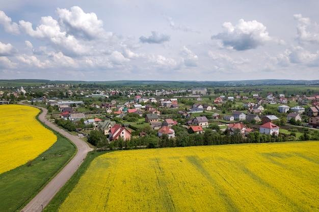 A vista aérea da estrada à terra em campos verdes com as plantas de florescência da colza, as casas do subúrbio no horizonte e o céu azul copiam o fundo do espaço. fotografia de zangão.