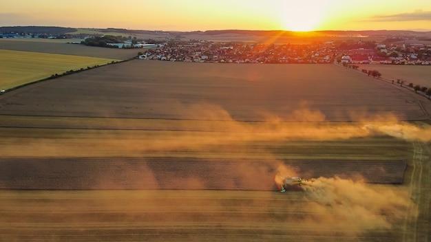 A vista aérea de colheitadeiras modernas trabalhando em um campo combina a colheita de trigo no campo ao pôr do sol