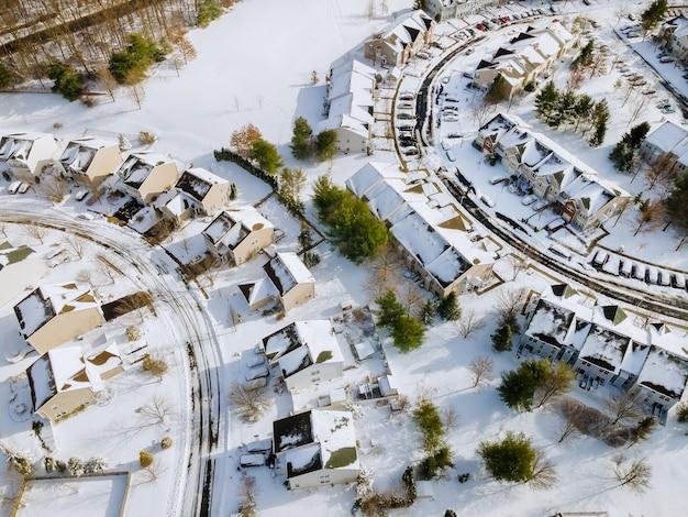 A vista aérea de inverno das casas no telhado dos pátios residenciais de uma pequena cidade coberta de neve