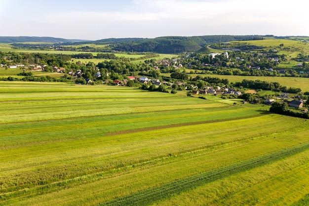 A vista aérea de uma pequena aldeia ganha muitas casas e campos agrícolas verdes na primavera com vegetação fresca após a temporada de semeadura em um dia quente e ensolarado.