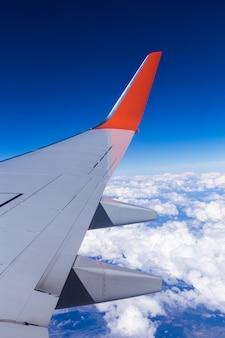 A vista aérea do céu azul da nuvem e o avião voam a vista através da janela do avião.