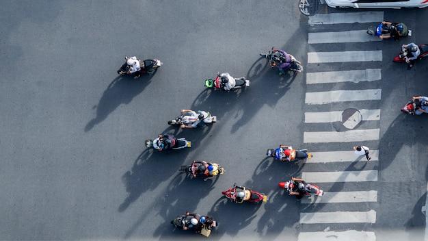 A vista aérea superior de motociclistas do borrão monta as motocicletas para passar a faixa de travessia pedestre na estrada com o signage do teste padrão do tráfego na rua.
