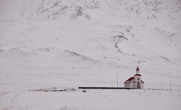 A vista cênico da igreja só no inverno após a tempestade de neve em islândia.